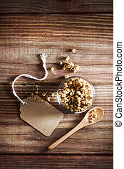 Dried Chamomile Tea in a small glass bowl on a rustic wooden...