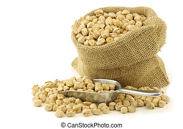dried chick peas in a burlap bag with an aluminum scoop on a white background