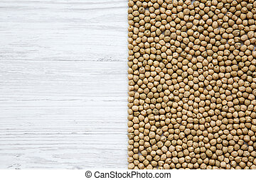 Dried chick peas on white wooden background, top view. Copy space.