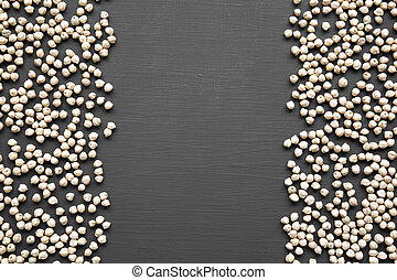 Dried chickpeas on a black wooden background, top view. Copy space.
