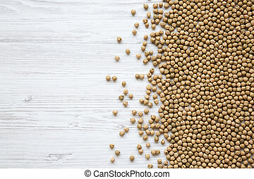 Dried chickpeas on a white wooden background, top view. Copy space.