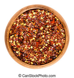 Dried chili pepper flakes in wooden bowl over white