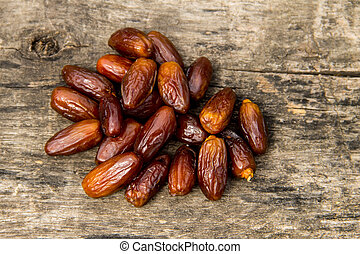 Dried date fruits on wooden background. Top view
