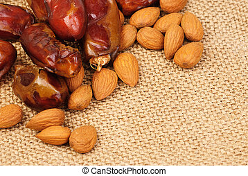 dried dates and almonds on canvas background