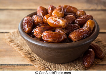 Dried dates fruit in ceramic bowl on wooden table.