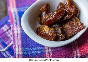 Dried dates in bowl on wooden table