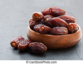 Dried dates in wooden bowl on black stone background