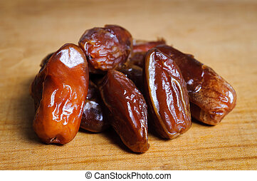 Dried dates on a wooden plate