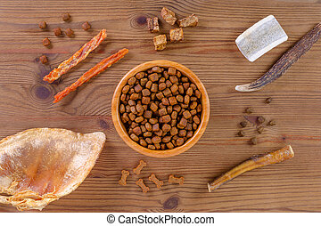 dried dog food in a bowl and different snack, chicken filet, antlers, lung, ear on white, flat lay