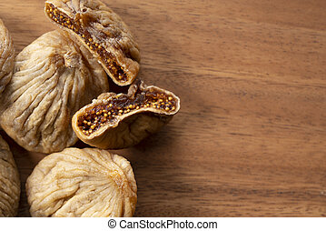 A top view of dried figs placed against a spacey wooden background