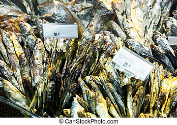 Closeup of various air-dried fish for sale on counter of fish shop..