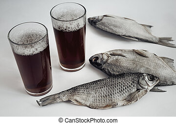 On the bright surface of my Desk is a dried fish, standing next to a glass of beer.