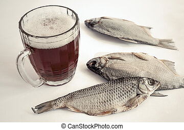 Dried fish on the table and a glass of beer