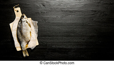 Dried fish on wooden board. On black chalkboard. Free space...