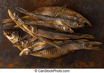 Dried fish. Salty dry river fish on a rusty metal plate background.