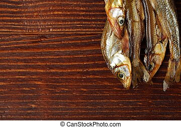 Dried fish with salt on wooden background