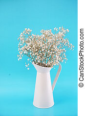 dried flower bouquet in metal vase with blue background