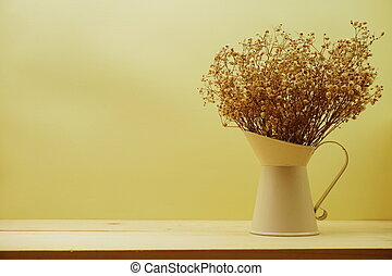 Dried flower bouquet in metal vase with yellow background