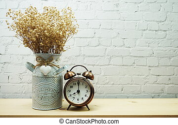Dried flower in metal vase and alarm clock with space copy on white brick wall background