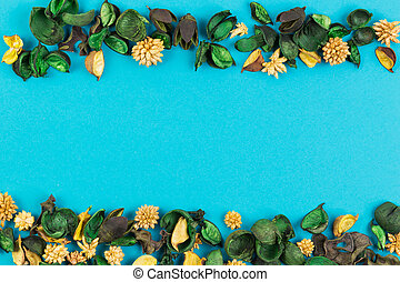 Dried flowers and leaves border frame on blue background. Top view, flat lay.