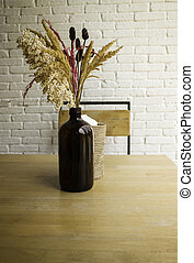 Dried flowers in a vase on wooden table