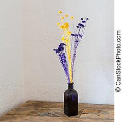 Dried flowers in blue bottle vase on wood