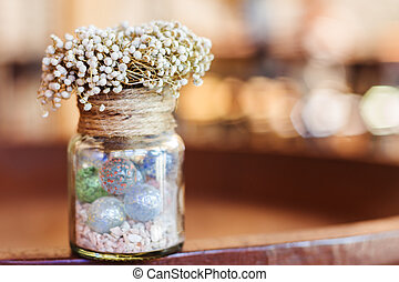 Dried flowers in glass bottle on wood table decorations in cafe.