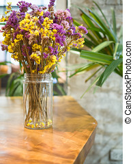 Dried flowers in vase on wooden table