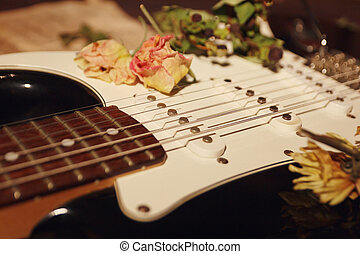 Dried flowers on electric guitar closeup. Selective focus.