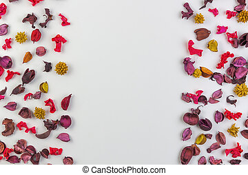 Dried flowers, petals and plants border frame on white background. Top view, flat lay.