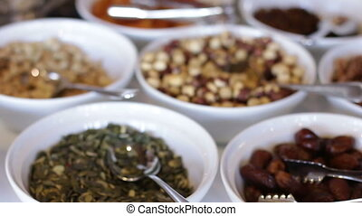 Dried fruit and nuts in clay bowls. pumpkin seeds and dates