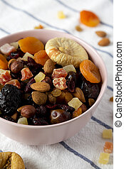 Dried fruits and nut mix in a pink bowl on cloth, side view. Close-up.