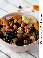 Dried fruits and nut mix in a pink bowl, side view. Close-up.