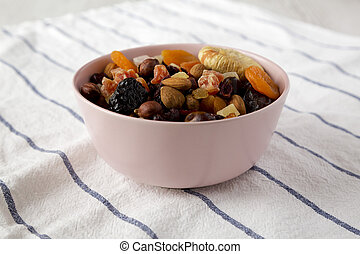 Dried fruits and nuts in a pink bowl, low angle view. Close-up.