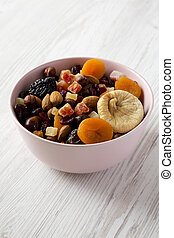Dried fruits and nuts in a pink bowl over white wooden background, low angle view. Close-up.