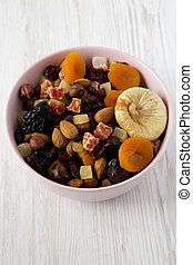Dried fruits and nuts in a pink bowl over white wooden surface, low angle view. Close-up.