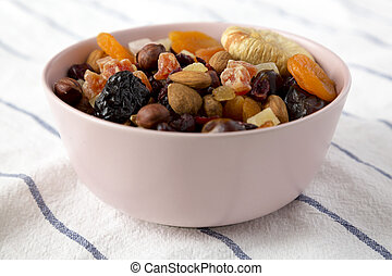 Dried fruits and nuts in a pink bowl, side view. Close-up.