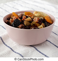 Dried fruits and nuts in a pink bowl, side view. Closeup.