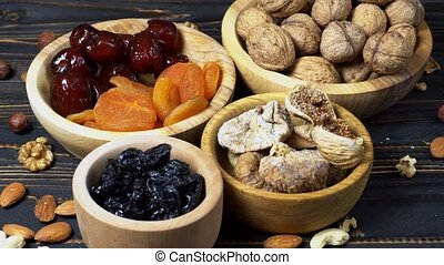 dried fruits figs, apricots, plums and nuts on wooden...