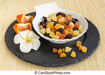 Dried fruits on stone plate with flower
