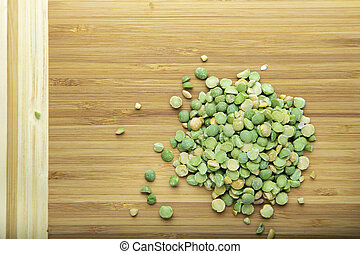 Dried green peas on a cutting board.