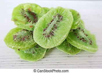 Dried kiwi fruit on white wooden background