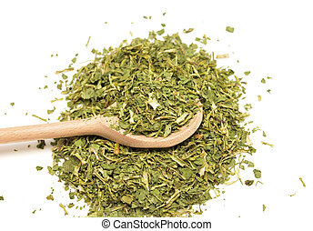 coriander - dried leaves of coriander in a wooden spoon ...