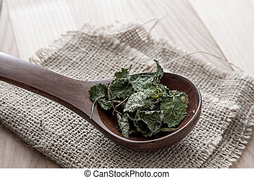 Dried lemon balm in wooden spoon, close up