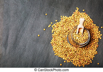 Dried lentils in a glass jar scattered on slate natural black background