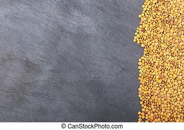 Dried lentils scattered on slate natural black background