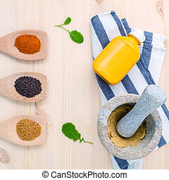 Dried mustard seeds black and yellow with turmeric powder in wooden spoons and mustard poder in the mortar on rustic wood background .Top view with copy space.