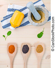 Dried mustard seeds black and yellow with turmeric powder in wooden spoons and mustard powder in the mortar on rustic wood background .Top view with copy space.