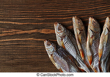 Dried or jerky salted roach, clipfish on wooden background. ...