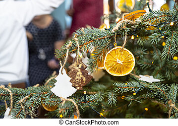 Dried orange slices and tree-shaped gingerbreads hanging on a Christmas tree, with Christmas lights and people in the background.